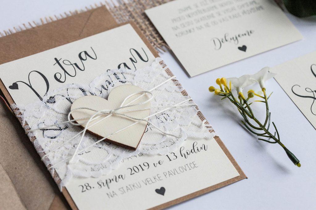 Rustikální svatební oznámení převázané krajkou s dřevěným srdcem