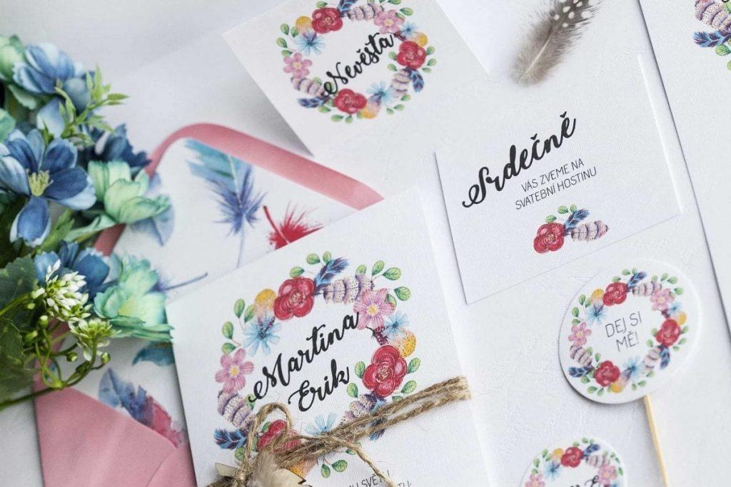 Boho svatební oznámení s květinovým věncem omotané přírodním provázkem a ozdobené dřevěným a pravým peříčkem