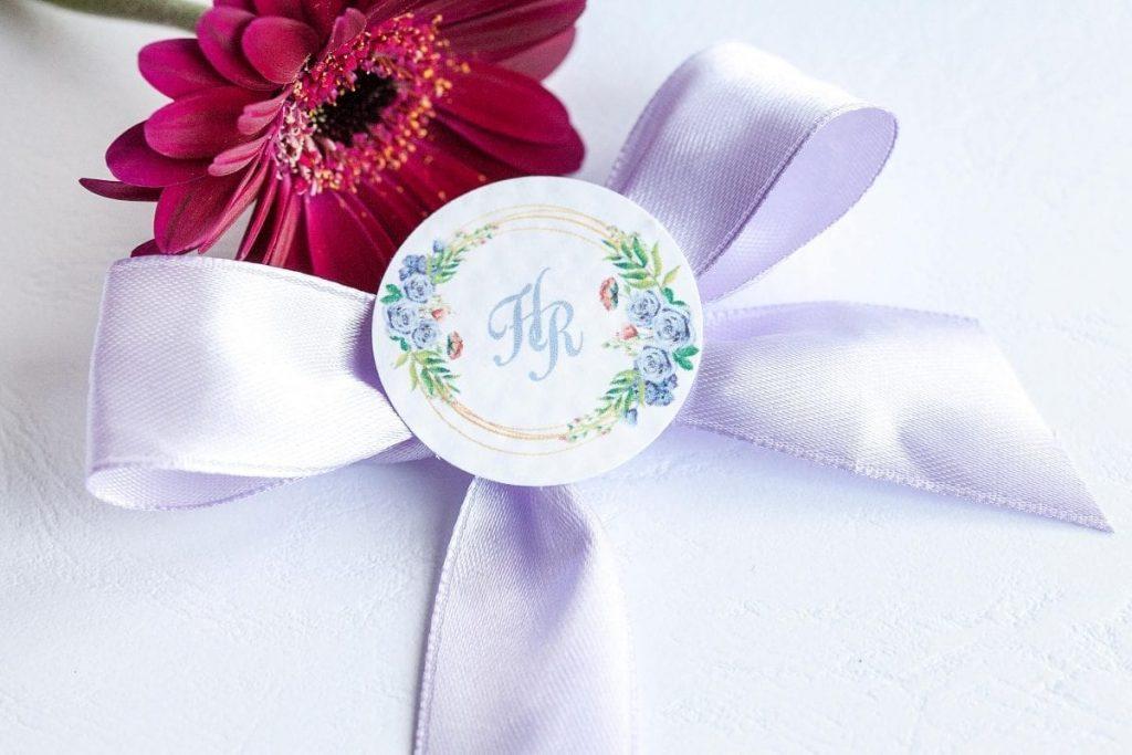 Svatební vývazek se stuhou a ozdobným kolečkem s iniciály lila